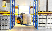 Forklift loader and worker at warehouse — Stock Photo
