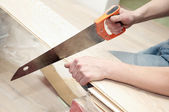 Hand saw cutting a board — Stock Photo