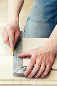 Carpenter works using metal angle — Stock Photo