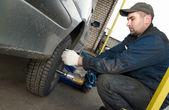 Machanic repairman at tyre replacement — Stock Photo