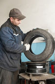 Repairman lubricating car tyre — Stock Photo