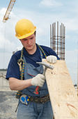 Builder working with hammer and plywood — Stock Photo