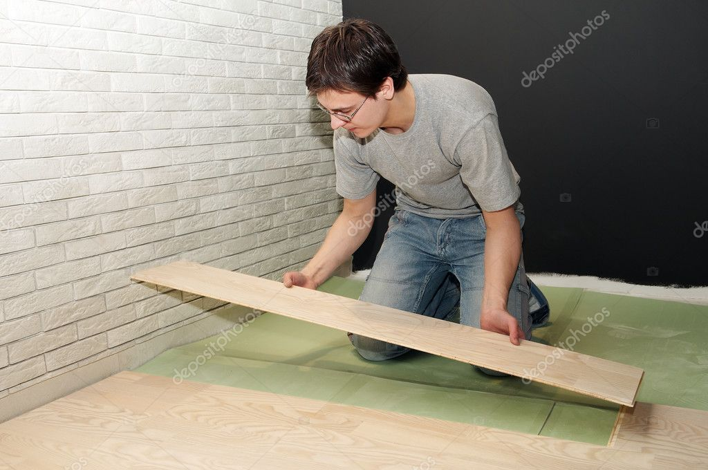 Young worker laying a floor with laminated flooring boards — Stock Photo #3245773