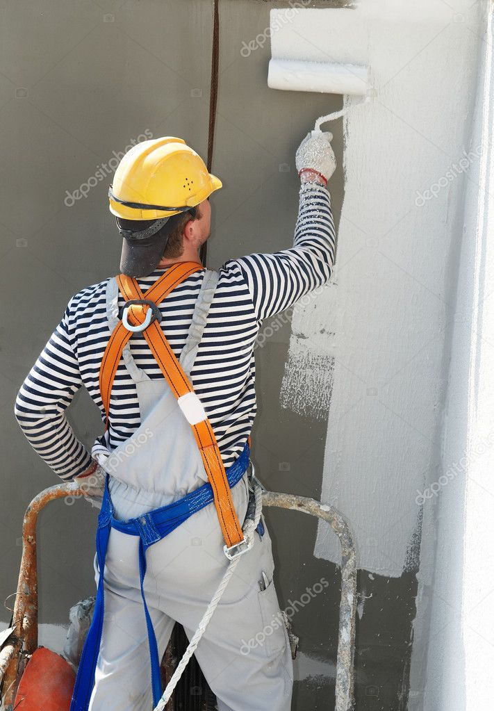 Builder worker painting facade of high-rise building with roller  Foto Stock #3245781