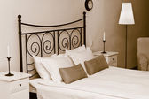 Forged headboard of bed with pillows — Stock Photo