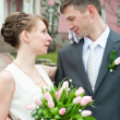 Young loving wedding couple with bunch of flower — Stock Photo