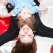 Foto Stock: Young mother and little child laying on back