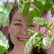 Young woman smelling flower in branch of tree — Stock Photo