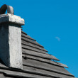Stock Photo: Chiney on wooden roof of house on blue sky