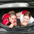 Two young women in car boot happy and smiling - Stock Photo
