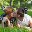 Young loving couple teenagers lying on green — Stock Photo #3166308