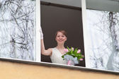Young bride in home window opening with flowers — Stock Photo