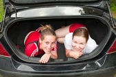 Two young women in car boot happy and smiling — Stock Photo
