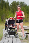 Young mother and sleeping baby in perambulator on planked footway in nature — Stock Photo