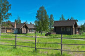 Russian village in summer time with buildings and fence — Stock Photo