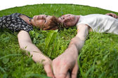 Young loving couple teenagers laying on grass — Stock Photo