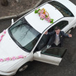 Stock Photo: Groom receive bride with open near white wedding car.