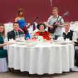 Five young at round white table in restaurant and two artists — Stock Photo