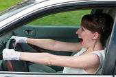 Woman in white dress and white-gloved sitting in car as a driver. — Stock Photo