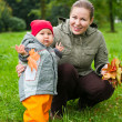 Woman a mother and little child walking in autumn park together — Stock Photo #3347638