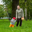 Woman a mother and little child walking in autumn park together — Stock Photo