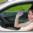 Woman in white dress and white-gloved sitting in car as a driver — Stock Photo #3347644