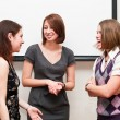 Three students a women talking togther in office room — Stock Photo #3347645