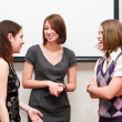 Three students a women talking togther in office room — Foto Stock
