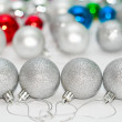 Four grey Christmas balls on foreground and many color balls on background — 图库照片