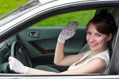 Woman in white dress and white-gloved sitting in car as a driver — Stock Photo