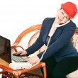 The girl in a red helmet with the laptop sits at a table and calling by pho - Stock Photo