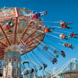 Action photo of carousel on blue sky - Stock Photo