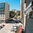 Optical camera on wall of building watching on parking - Stockfoto