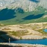 hombre en la montaña cerca del lago de pie y mirando a cámara desde lejos — Foto de Stock   #3587674