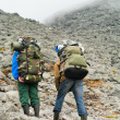 Two tired backpackers in mountains with knapsacks — Stock Photo