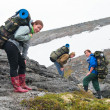 Tired team of backpackers in mountains with knapsacks — Stock Photo