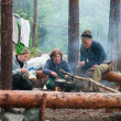 Hikers cook on fire in forest — Stock Photo
