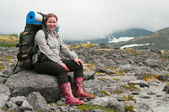 Backpacker a young woman sitting on rock in mountains — Foto de Stock