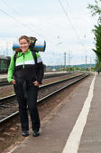 Backpacker a young woman waiting train on railway station — Stock Photo