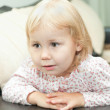 Little child a dlond girl sitting on sofa and looking through — Stock Photo