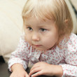 Little child a blond girl sitting on sofa and looking through — Foto de Stock