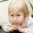 Little child a blond girl sitting on sofa and looking through — Stock Photo