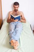 Człowiek czytając książkę na łóżku — Zdjęcie stockowe