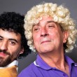 Foto Stock: Young and Senior Man with Wig Making a Face