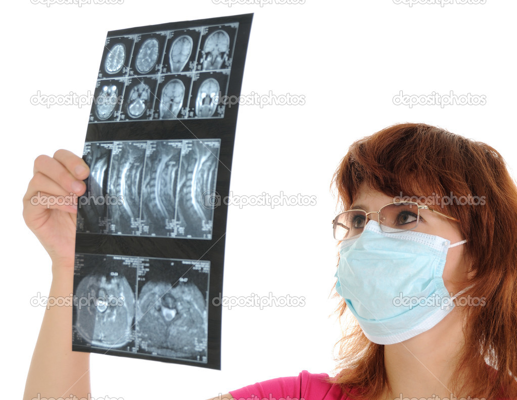 Young female doctor with mask looking at tomogram — Stock Photo #3896667