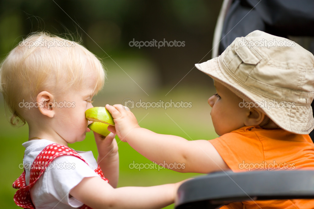 Two kids with apples outdoors looking after each other  Stock Photo #3857123