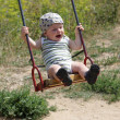 Happy baby is swinging — Stock Photo