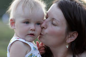 Mother kisses her little baby — Stock Photo