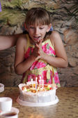 Excited girl looks on cake — Stock Photo