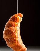 Fresh croissant with honey — Stock Photo